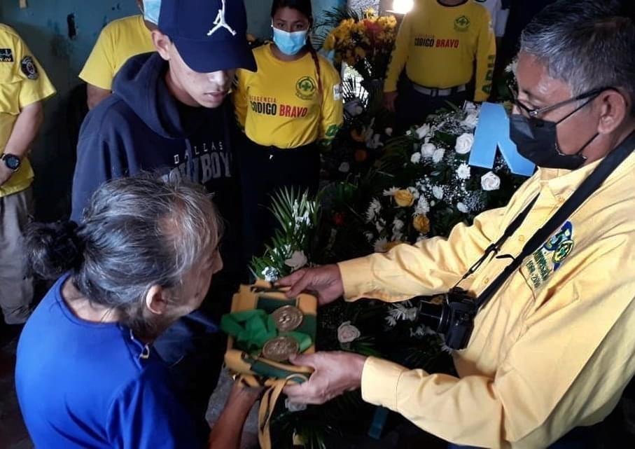 Campos entrega medal a mamá de manuel.